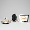 A silver and glass inkwell and two silver frames.