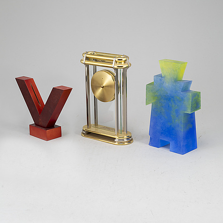 A collection of three sculptures and a mantel clock.