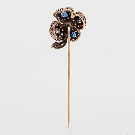 A four-leaf diamond and sapphire stick pin in platinum and 14k gold.