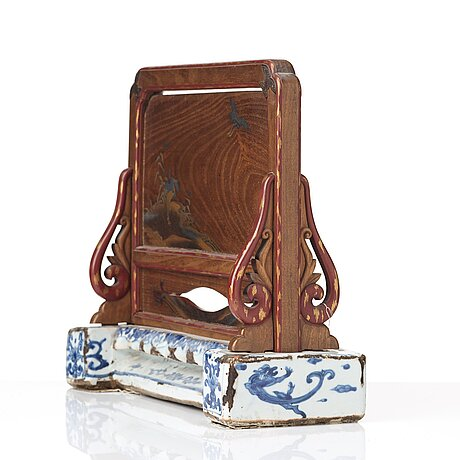 A japanese wooden and lacquered table screen on a blue and white ming dynasty porcelain base.
