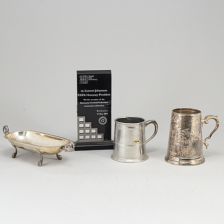 A white metal sculpture, a cup and a bowl.