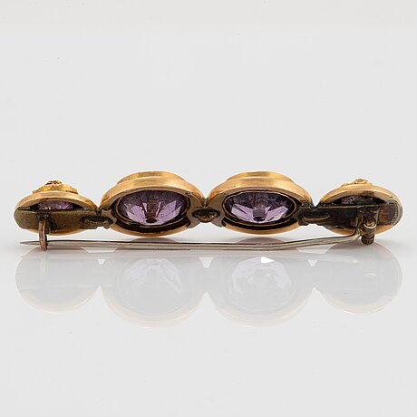 An 18k gold and amethyst brooch set with pearls and with black enamel decoration.