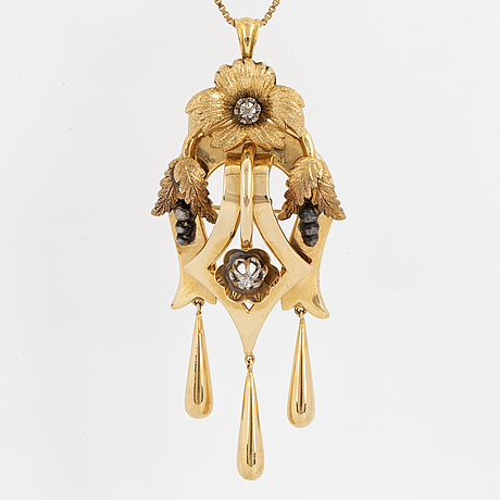 An 18k gold and silver brooch/pendant set with diamonds.