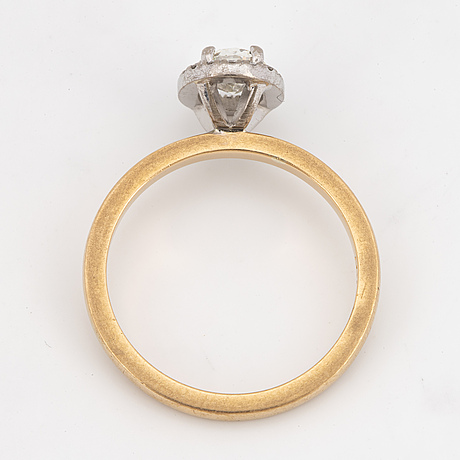 An 18k gold ring set with an oval brilliant-cut diamond.