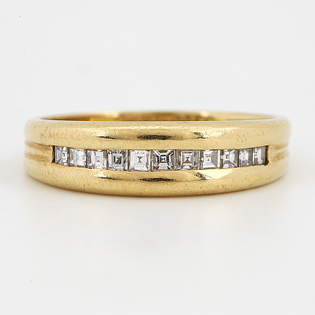 An 18k gold ring set with step-cut diamonds.