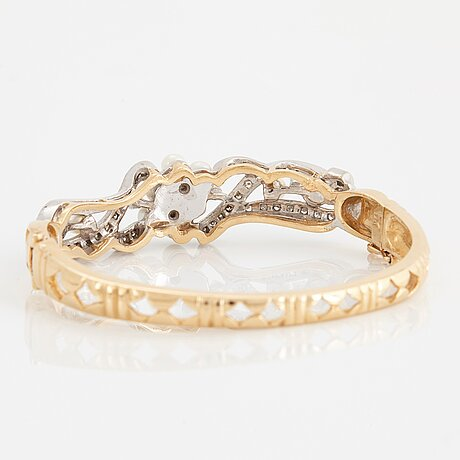 A 14k gold bangle set with old- and eight-cut diamonds and pearls.