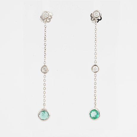 A pair of 18k white gold set with faceted emeralds.