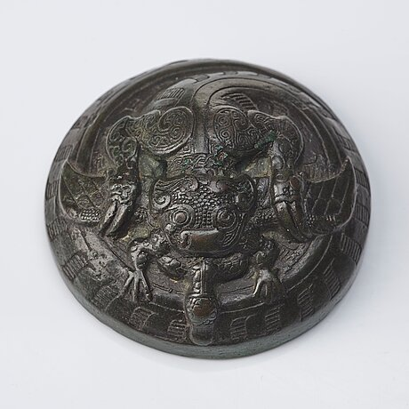 A bronze dragon a and bird weight, warring states (475–221 bc).