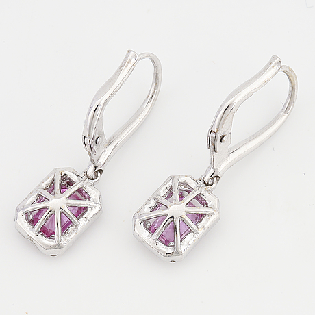A pair of 18k gold earrings set with faceted pink sapphires.