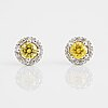 A pair of 18k gold earrings set with color treated yellow diamonds.
