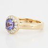An 18k gold ring set with a faceted tanzanite and round brilliant-cut diamonds.