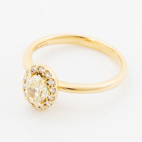Oval light yellow diamond and brilliant-cut diamond ring.