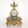 A mid-19th-century french gilt-brass mantel clock with a pair of candelabra by dussault.