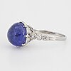 Cabochon-cut tanzanite and brilliant-cut diamond ring.