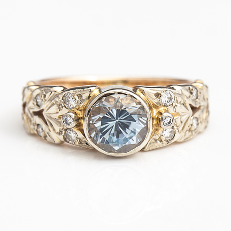 An 14k gold ring with diamonds ca. 0.18 ct in total and a topaz.