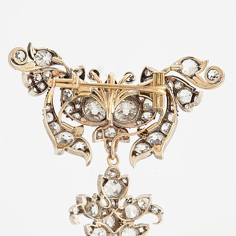 A 14k gold and silver brooch set with old-cut diamonds.