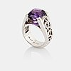 An 18k white gold ring set with a faceted amethyst and round brilliant-cut diamonds.