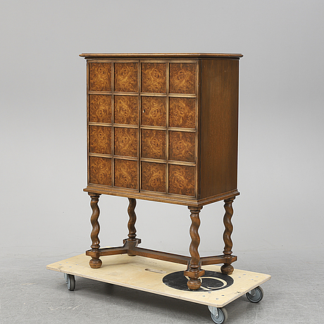A baroque style oak cabinet dated 1947.