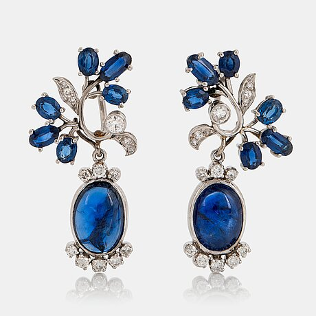 A pair of cf carlman platinum earrings set with cabochon-cut and faceted sapphires.