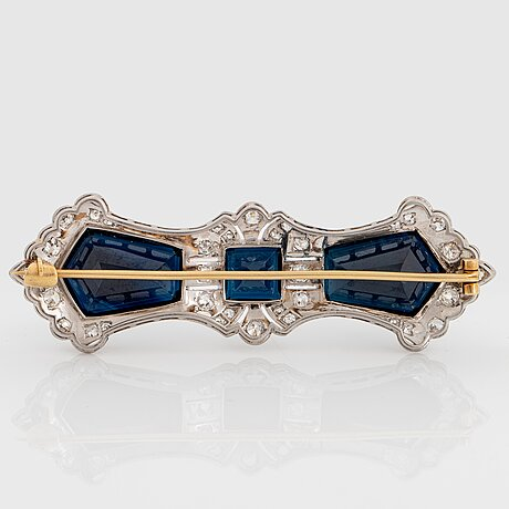 An 18k gold brooch set with step-cut sapphires with a total weight of ca 40.00 cts.