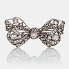 A silver bow brooch set with old-cut diamonds.
