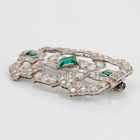 A platinum brooch set with old-cut diamonds and faceted green paste.