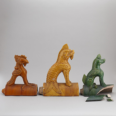 A group of three chinese glazed roof tiles of seated animals, 20th century.