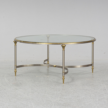 An end of the 20th century coffee table with a glass top.