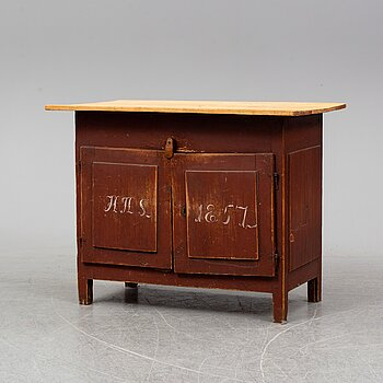 A painted table with cabinet, dated 1857.