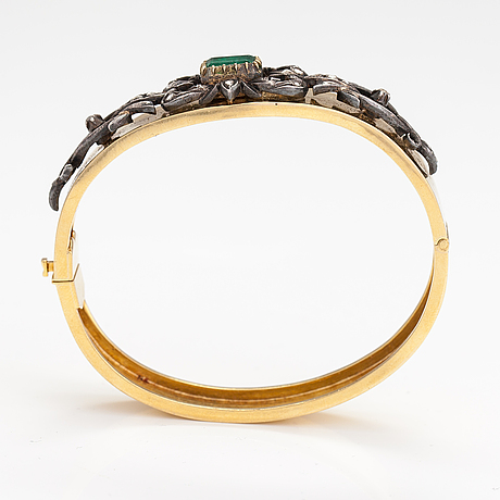 An 18k gold and silver bracelet with an emerald ca. 1.05 ct and rose cut diamonds.