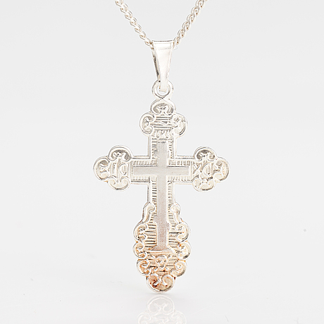 A stelring silver necklace with a cross.