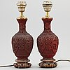 A pair of chinese red lacquered vases, turned into table lamps, 20th century.