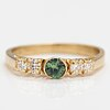 An 18k gold ring with a green sapphire and diamonds ca. 0.24 ct in total. finnish import marks, 1987.