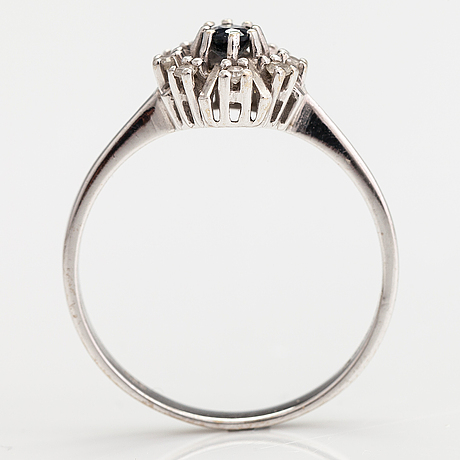 A 14k white gold ring with a sapphire and diamonds ca. 0.08 ct in total. import marked mauri hyvärinen, 1986.