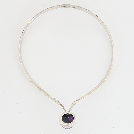 A silver necklace set with an amethyst.
