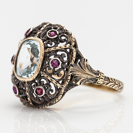 An 14k, 18k gold and silver ring with an aquamarine, rubies and two red glass stones.
