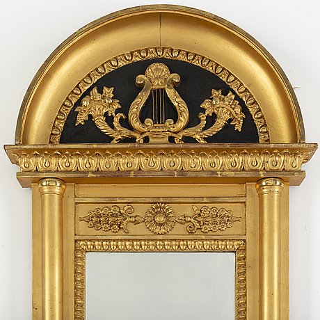 A 20th century empire style gilt mirror.