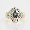 An 18k gold ring set with a synthetic sapphire and round brilliant-cut diamonds.