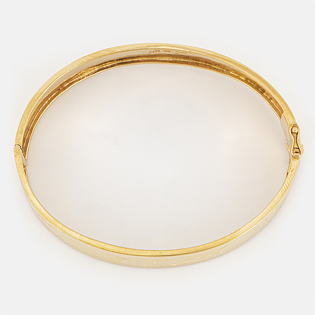 An 18k gold bangle.