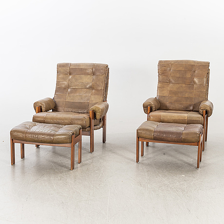 A pair of 1970/80:s easy chairs with stools.
