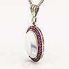 A 14k gold and silver necklace with a moon stone, rubies and a red glass stone.