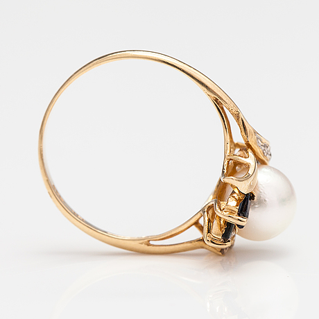 A 14k gold ring with a cultured pearl, sapphires and diamonds ca. 0.06 ct in total.