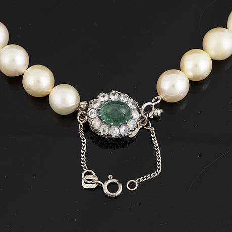 Cultured pearl necklace, clasp 18k white gold with cabochon emerald and white stones.