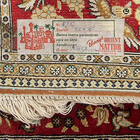 A silk rug from qum, around 75 x 54 cm.