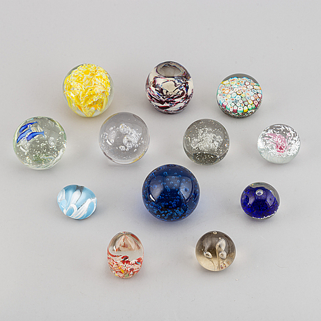 A group of 12 glass paper weights.