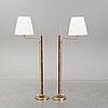 A pair of brass and leather floor lights.
