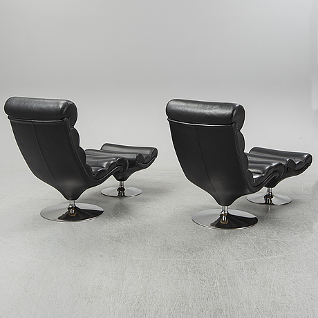 A pair of leather easychairs with stools from the late 20th century.