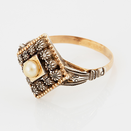 An 18k gold and silver ring set with a pearl and rose-cut diamonds.