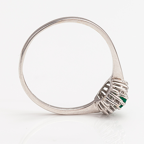 A 14k white gold ring with an emerald and diamonds ca. 0.12 ct in total. finnish import marks.