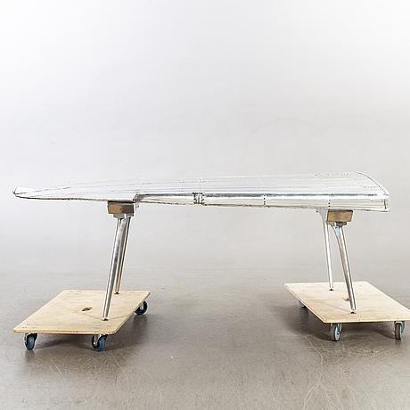 A writing desk, a wing from an dakota7dc3/c-43 air craft.